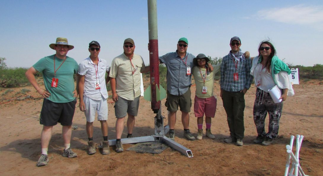 Students pose with rocket
