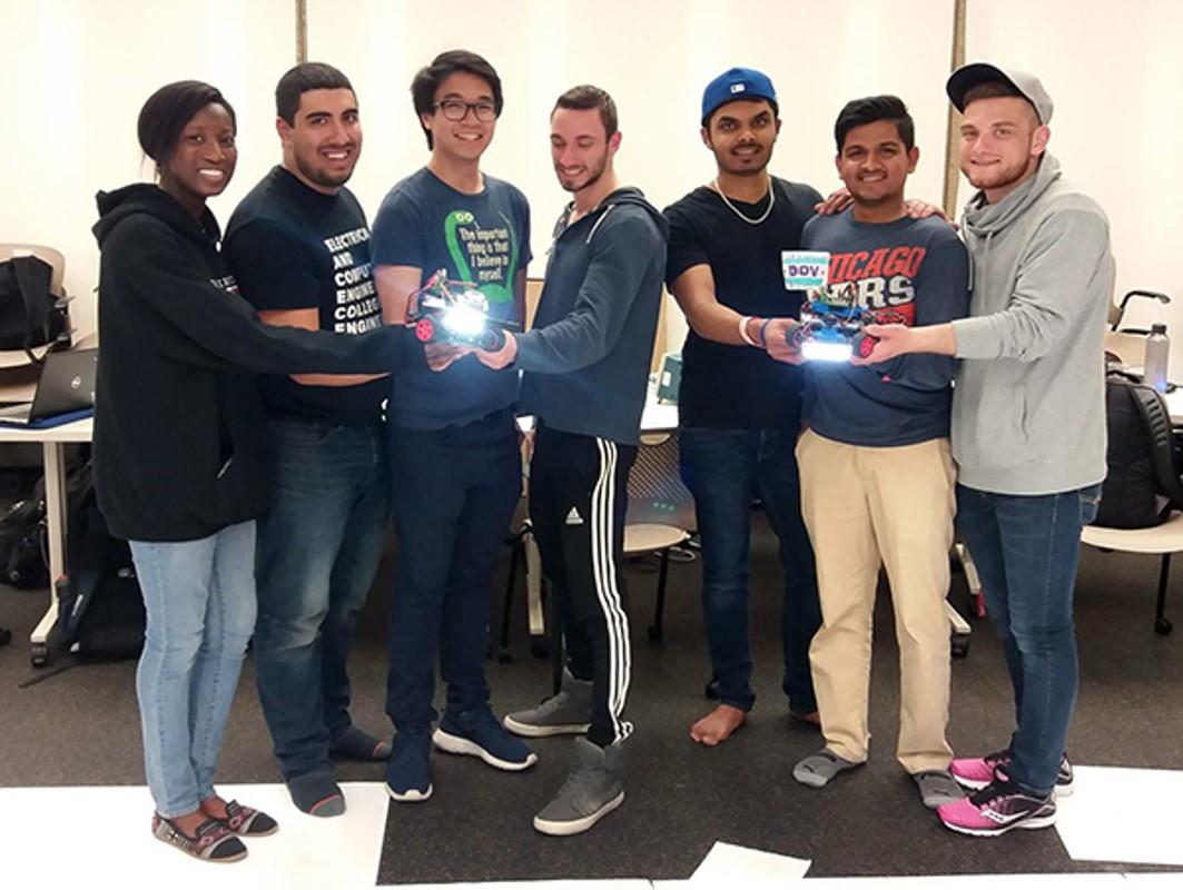 Students holding autonomous cars