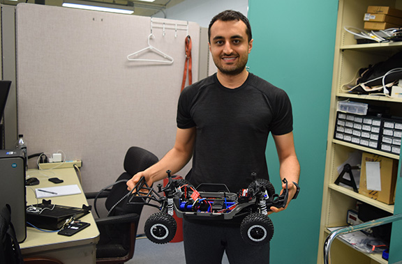 Student holding car prototype