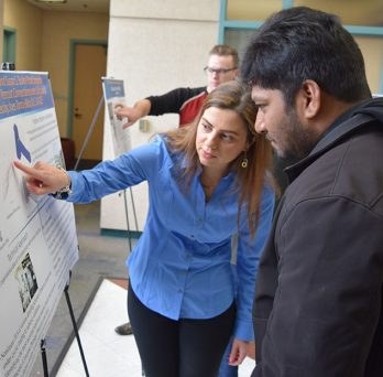 Students observe posters at competition