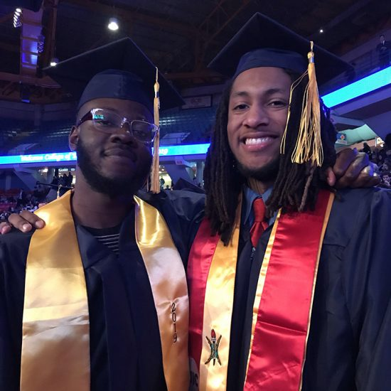 two students at commencement ceremony