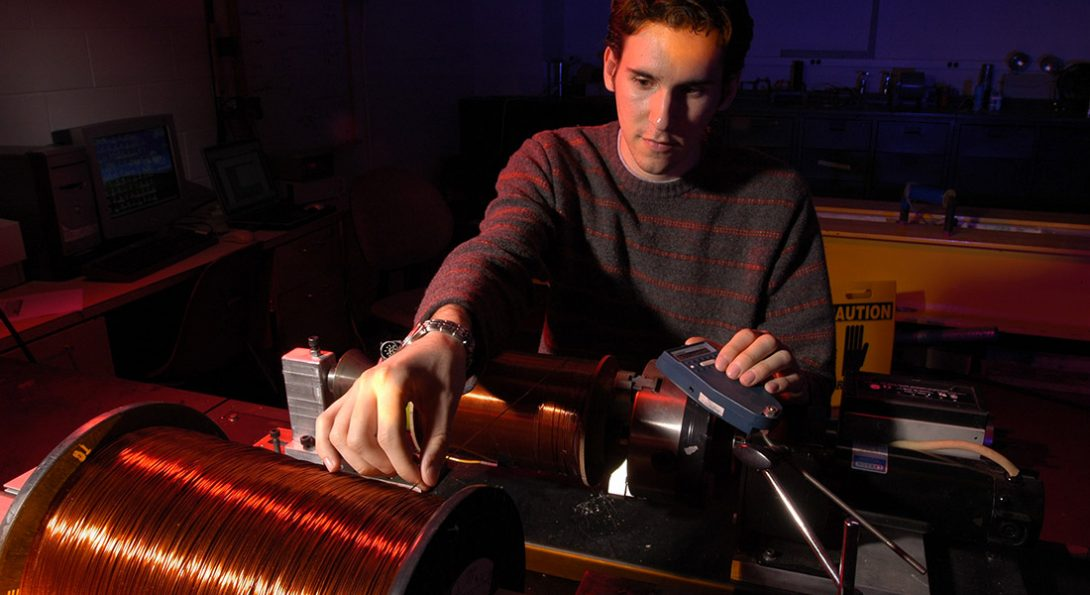 student with machinery and large spool of wire