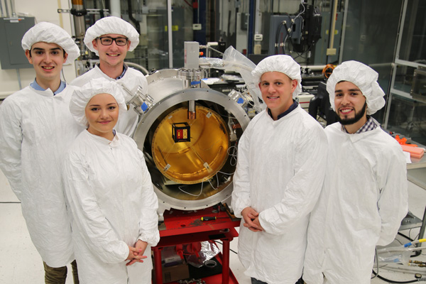Team in front of vessel in Fermilab's cleanroom
