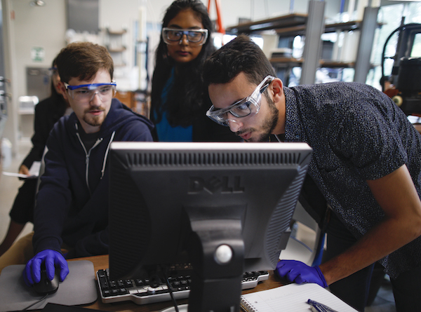 three students working on a computer in the Engineering Innovation Building