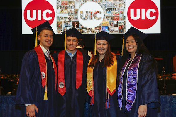 four students at engineering commencement
