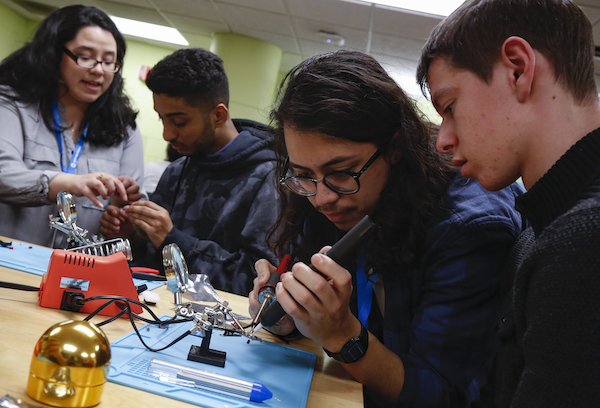 students work on a soldering activity in the Tinkering Club