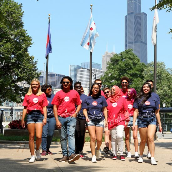students representing all backgrounds at the northeast gate of East Campus, with the Sears Tower in the background