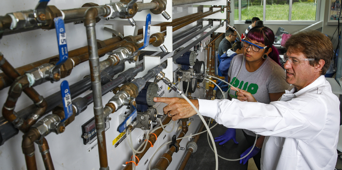 Professor instructs student on working with industrial pipes in Chemistry lab