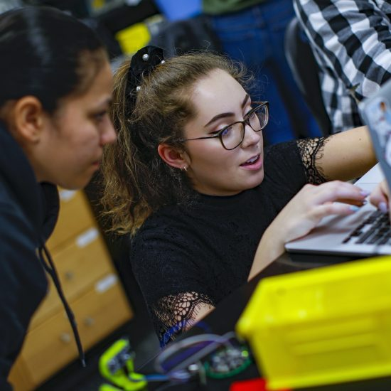 Two students collaborating at a laptop