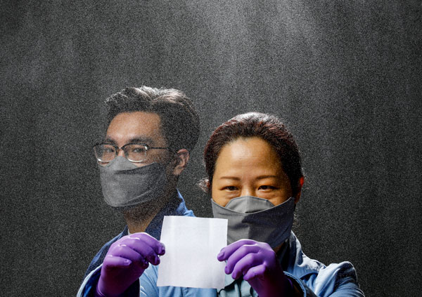 Two researchers, one wearing gloves and holding up a square piece of material