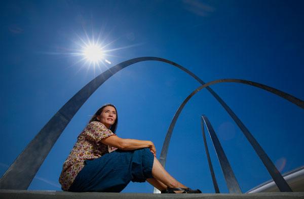 Miiri Kotche sitting beneath a sculpture
