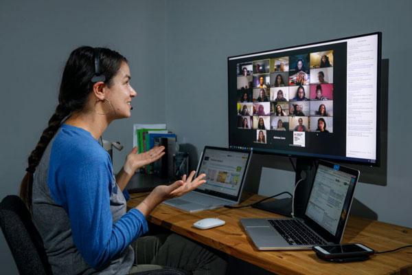 Person sitting at a workstation facilitating a virtual meeting