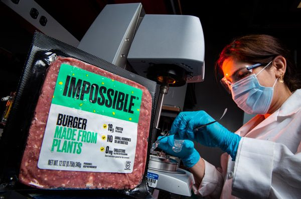 A package of plant-based meat next to a researcher using machinery