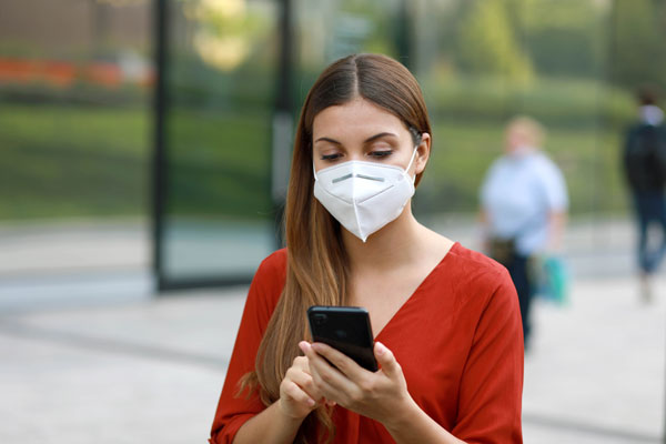 Person holding a cellphone and wearing a face mask