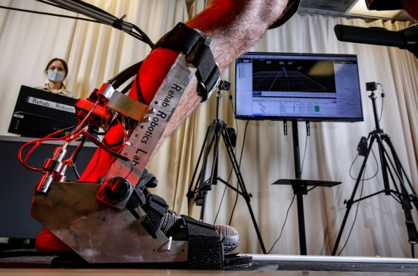 MIE assistant professor Myunghee Kim monitors the wearing and use of the two degree-of-freedom robotic ankle-foot orthosis to assist occupational workers in Chicago