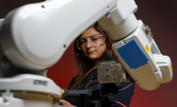 a female graduate student programming a large robotic arm