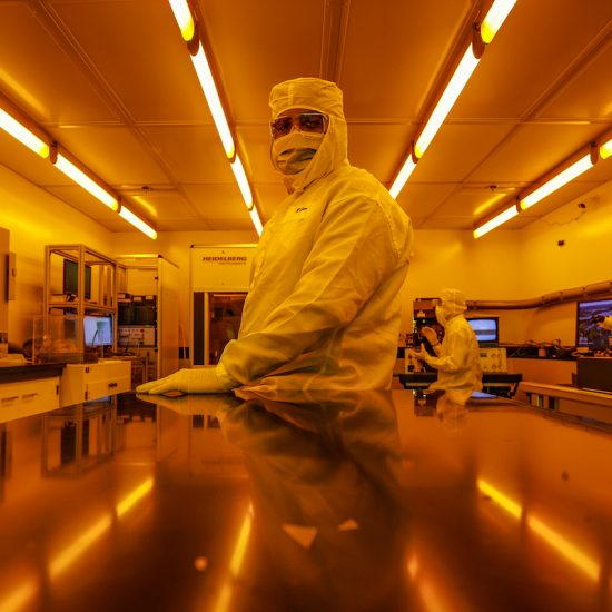 A researcher poses under the yellow interior lights of a Nanotechnology Core Facility room